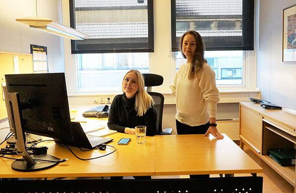 2 damer ved et skrivebord foran en laptop og en skjerm. 1 dame sitter og den andre står.