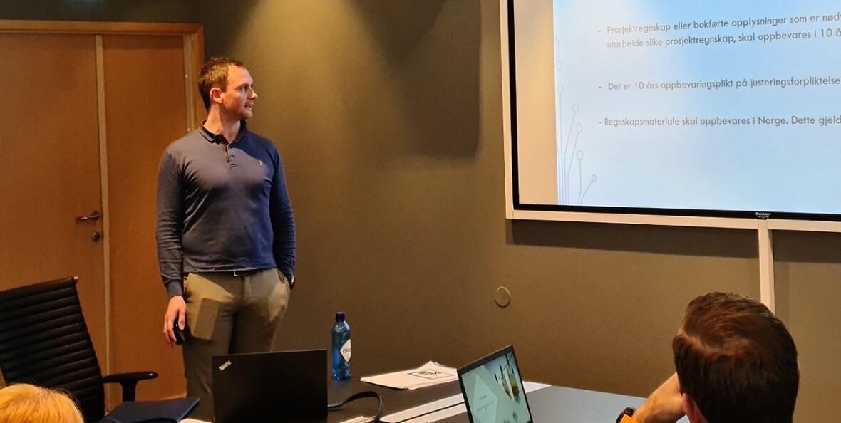 En mann som står og viser en presentasjon på en stor skjerm.