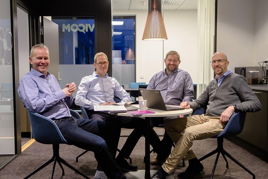 4 menn sitter rundt et bord på et kontor.